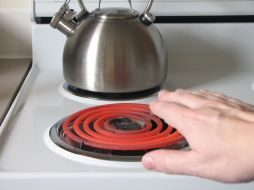 Hand approaches hot burner